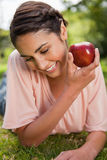 Woman looking downwards while presenting an apple Royalty Free Stock Image