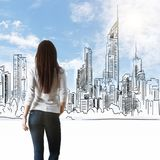 Woman looking at drawn city. Back view of thoughtful young woman looking at drawn city on blue sky background royalty free stock images