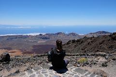 Woman looking at a dry and rocky volcanic landscape on Teide - Spain stock photos