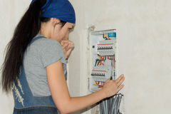Woman looking at an electrical fuse board. DIY woman looking at an electrical fuse board Royalty Free Stock Photography