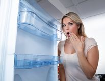 Woman Looking In Empty Fridge. Photo Of Young Woman Looking In Empty Fridge stock photo
