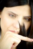 Woman looking ends of hair to see if it is ruined Royalty Free Stock Photography