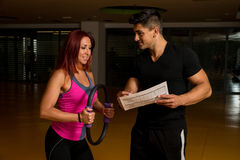 Woman looking at exercise charts with fitness trainer Stock Images