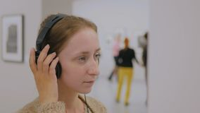 Woman looking at exposition and listening audio guide in modern photo gallery stock footage