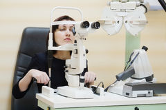 Woman looking into eye test machine Royalty Free Stock Photography