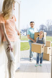 Woman looking at family with cardboard boxes entering new home Royalty Free Stock Photo