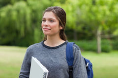 Woman looking far away while standing in a park wi Stock Photo