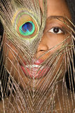 Woman looking through feather. Close-up smiling African-American mid-adult woman looking through peacock feather Stock Image