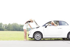 Woman looking at female friend repairing broken down car on country road Royalty Free Stock Photos