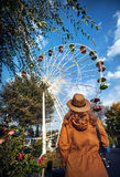 Woman looking at Ferris wheel in the park Stock Photo