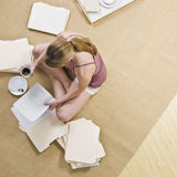 Woman Looking through Files. A woman is seated on the floor, looking through files, and drinking coffee.  Square framed shot Royalty Free Stock Photography