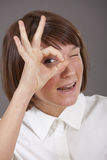 Woman looking through fingers stock image