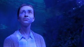 Woman looking at fish in large public aquarium tank at Oceanarium. Portrait of woman looking at fish in large public aquarium tank at Oceanarium with blue stock video