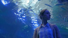Woman looking at fish vortex in large public aquarium tank at Oceanarium stock video