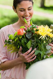 Woman looking at flowers. Which have been given to her Royalty Free Stock Image