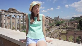 Woman looking at Forum Romanum. Female tourist enjoying vacation near Roman forum in center of Rome. Woman in hat looking at ancient ruins Forum Romanum in slow stock video footage