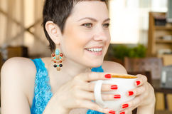 Woman looking forward, as she holds a mug Royalty Free Stock Photography