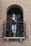 Woman looking forward standing on balcony. Of italian house Royalty Free Stock Image
