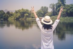 Woman looking forward to river with raising hands up and she has feeling relax and happiness. stock images