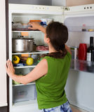 Woman looking in fridge. Brunette woman looking for something in fridge at home kitchen royalty free stock photo
