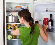 Woman looking in fridge. Young brunette woman looking for something in fridge at home kitchen stock images