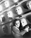 Woman looking frightened holding onto one mask on the wall of masks royalty free stock photos