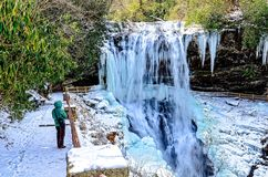 Woman Looking at a Frozen Waterfall. Woman hiker looking a a frozen waterfall on a cold wintry day royalty free stock photography