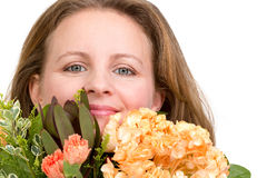 Woman Looking Genuinely in to your Eyes Behind the Flower Bouque Royalty Free Stock Photo