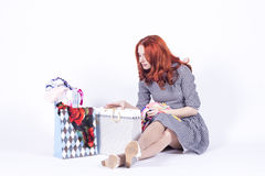 Woman looking at a gift bag with surprise Stock Images