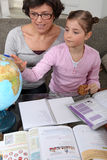 Woman looking at a globe. With a little girl Stock Photography