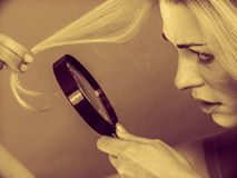 Woman looking at hair through magnifying glass Stock Photo