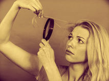 Woman looking at hair through magnifying glass Stock Image