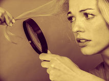 Woman looking at hair through magnifying glass Stock Photos