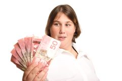 Woman Looking At Handfull Of Fifties. Woman looking at a fan of Canadian Fifty dollar bills in her hand Royalty Free Stock Photos