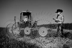 Woman looking at haying rake Stock Photography