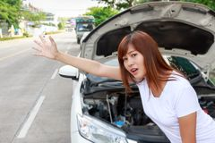 Woman looking for help after a car breakdown, standing besides c. Ar and hitching a ride Stock Image