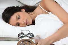 Woman looking her alarm clock Royalty Free Stock Photos