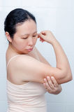 Woman looking at her arm Stock Image