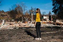 Woman looking at her burned home after fire disaster. Young owner woman checking burned and ruined house and yard after fire, consequences of fire disaster royalty free stock images
