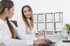 Woman is looking at her colleague with a smile Stock Images