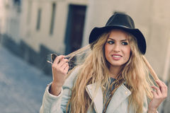 Woman looking with her curly blonde hair in urban background Royalty Free Stock Photo