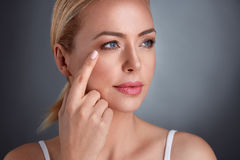 Woman looking at her facial wrinkles. Nourished middle age woman looking at wrinkles around the eyes royalty free stock photos