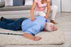 Woman Looking At Her Fainted Disabled Father. Shocked Young Woman Looking At Her Fainted Disabled Father Lying On Carpet Stock Photos