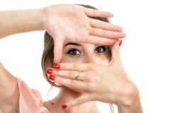 Woman looking through her fingers Royalty Free Stock Image