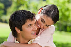 Woman looking at her friend while he is carrying her Stock Photo
