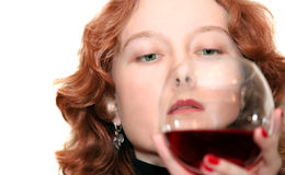 Woman looking at her glass of wine. Red-haired and green-eyed woman looking at her glass of wine Stock Photos