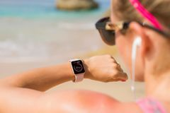 Woman looking at her heart rate data on smartwatch Stock Images