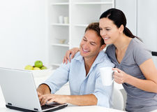 Woman looking at her husband working on the laptop. Affectionate woman looking at her boyfriend working on the laptop in the kitchen Royalty Free Stock Photo