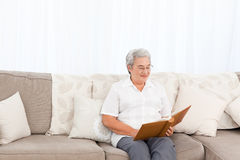 Woman looking at her photo album Stock Photos