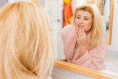 Woman looking at her reflection in mirror. Happy awaken woman standing in bathroom looking at her reflection in mirror after morning getting up stock photo
